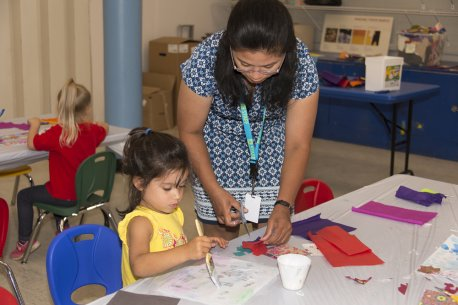 Teacher helping young students make collages in a classroom