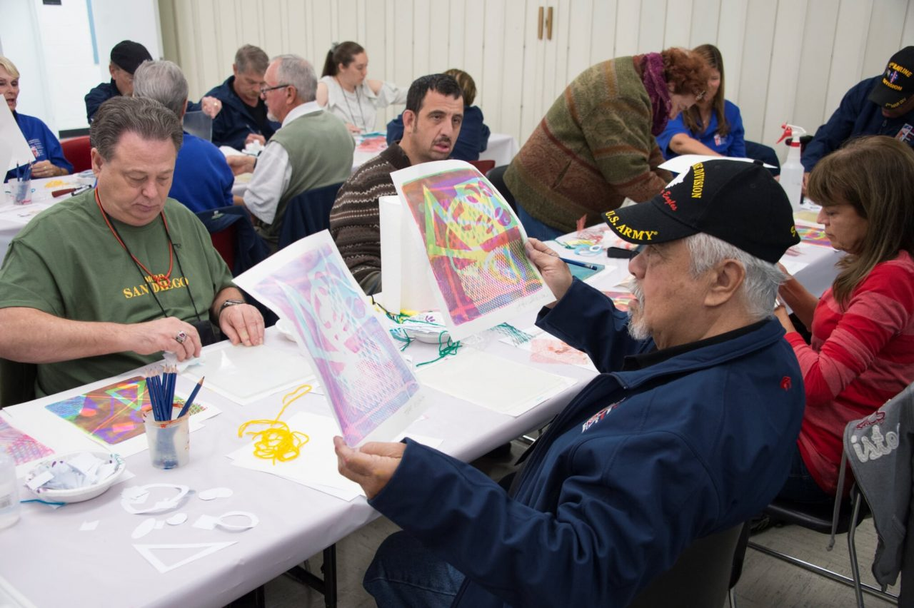 Adult men and women sit around tables in the classroom working on an art activity