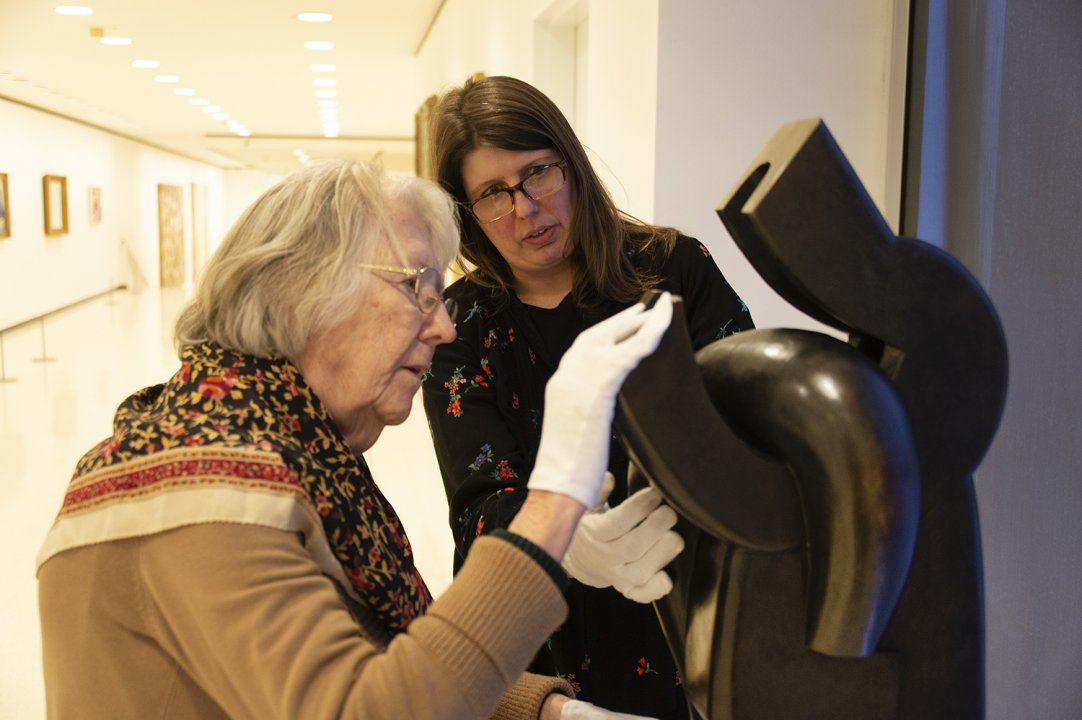 Access & Community Programs Coordinator Karen Duval helps a woman with white gloves on touch a sculpture