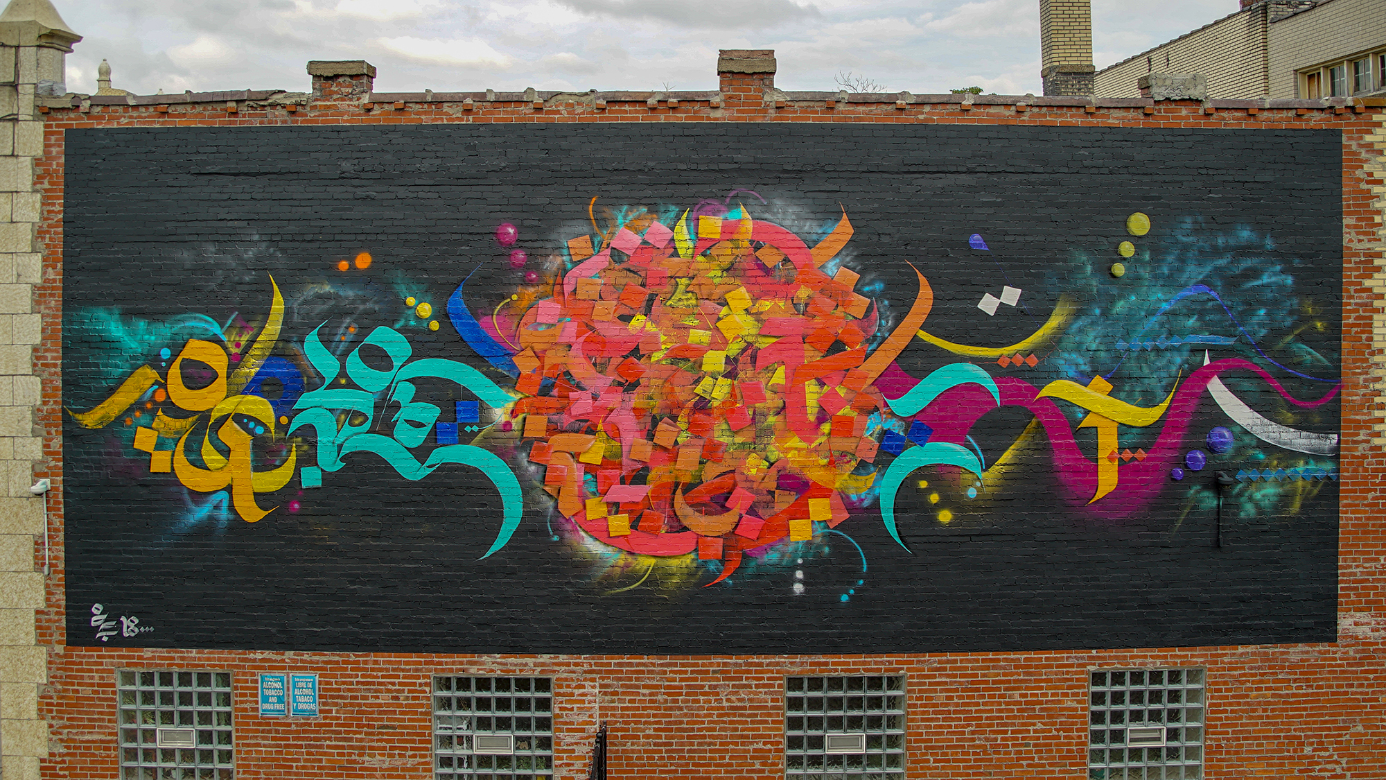A painted mural on a red brick building - the mural has a black background, an orange and yellow circular shape in the middle of marks of different colors on the sides