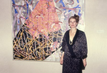 A color photograph of Nancy Graves in front of one of her artworks