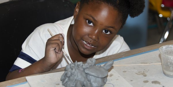 An African American girl making a ceramic animal