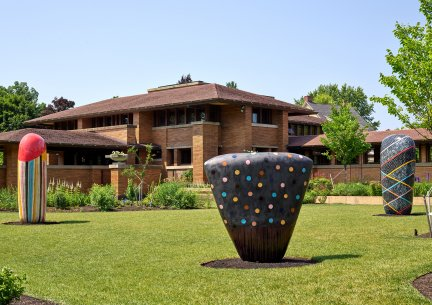 Three large ceramic sculptures in front of a brick house