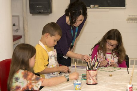 An instructor assists children with a painting project