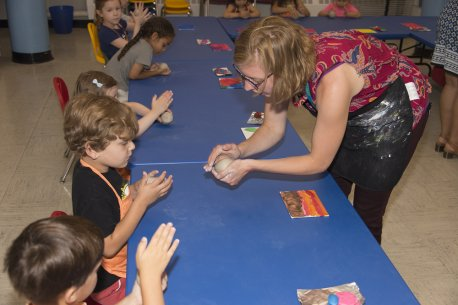 An AK educator show children how to work with clay