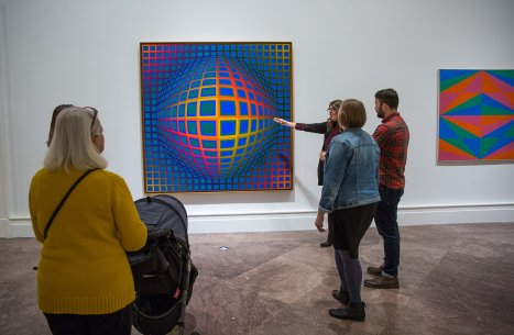 Several adults looking at Victor Vasarely's Op art painting Vega-nor