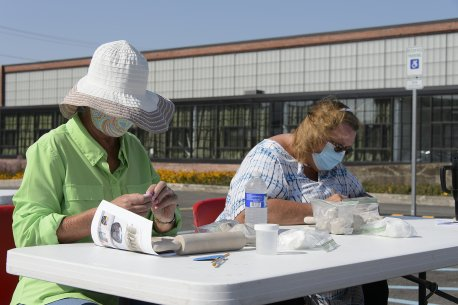Two white women wearing face masks seated at a table making ceramic beads