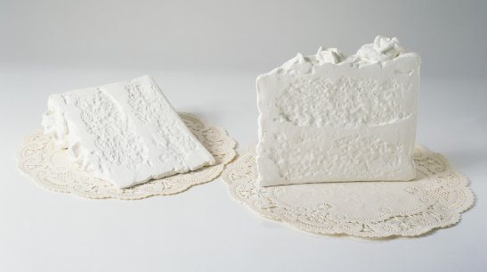 Two sculptures that look like all-white pieces of cake