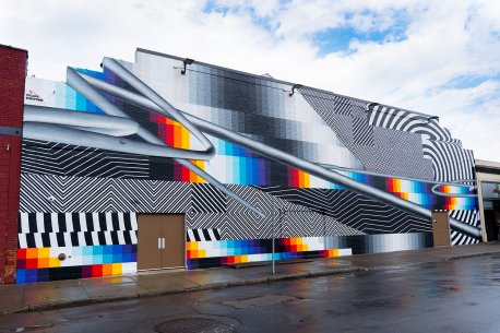 A mural on an exterior wall with sections of black and white and sections of different colored blocks