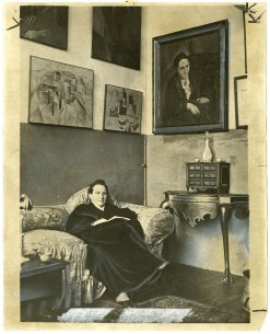 A black and white photograph of a woman sitting on a cough with paintings hanging on the wall behind her