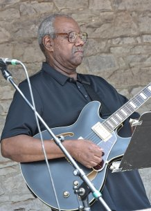 An African American man in a blue shirt playing a blue guitar