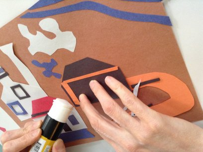 A person gluing paper shapes onto a sheet of brown paper