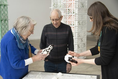 An older woman and a younger woman hold glass bottles with clay seashells glued to them while an older man looks on