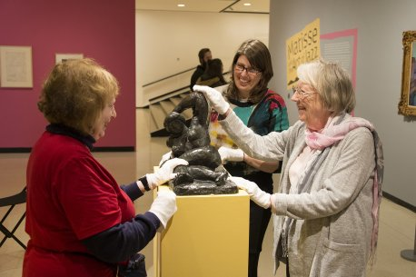 A tour guide and visitors touching a sculpture with white gloves on