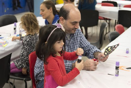 A father and daughter making a collage in the classroom