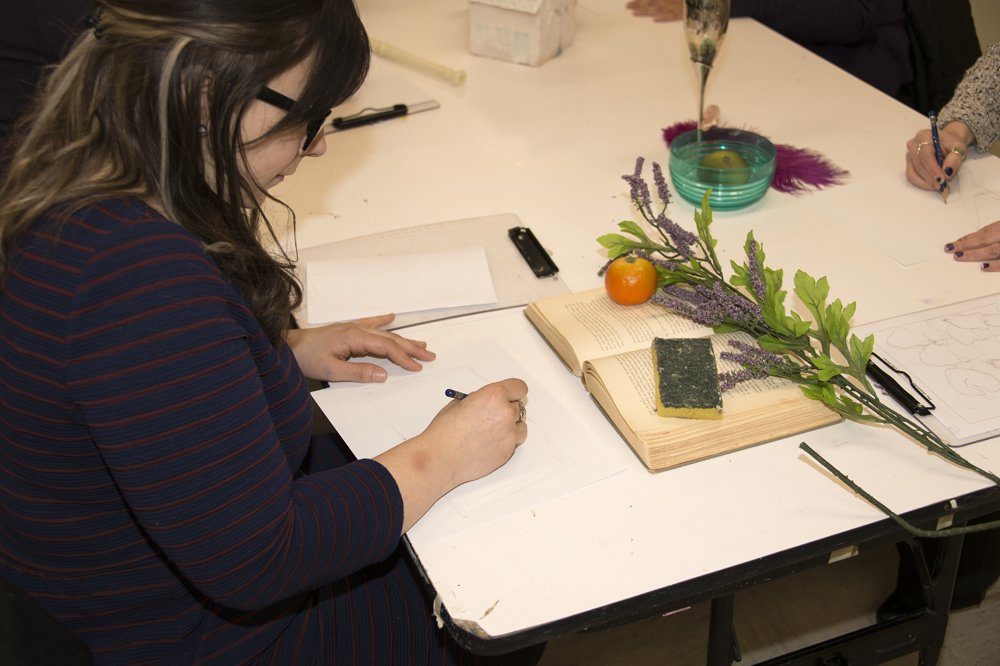 A woman makes a still life drawing in the education classrooms