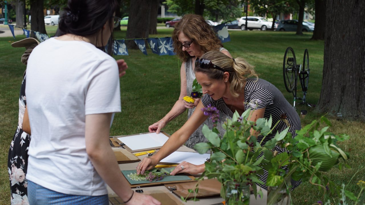 Community members at work during Garden Walk Buffalo 2019 on some of the cyanotypes that will serve as the inspiration for Hillary Waters Fayle's 244 Dewitt Street mural
