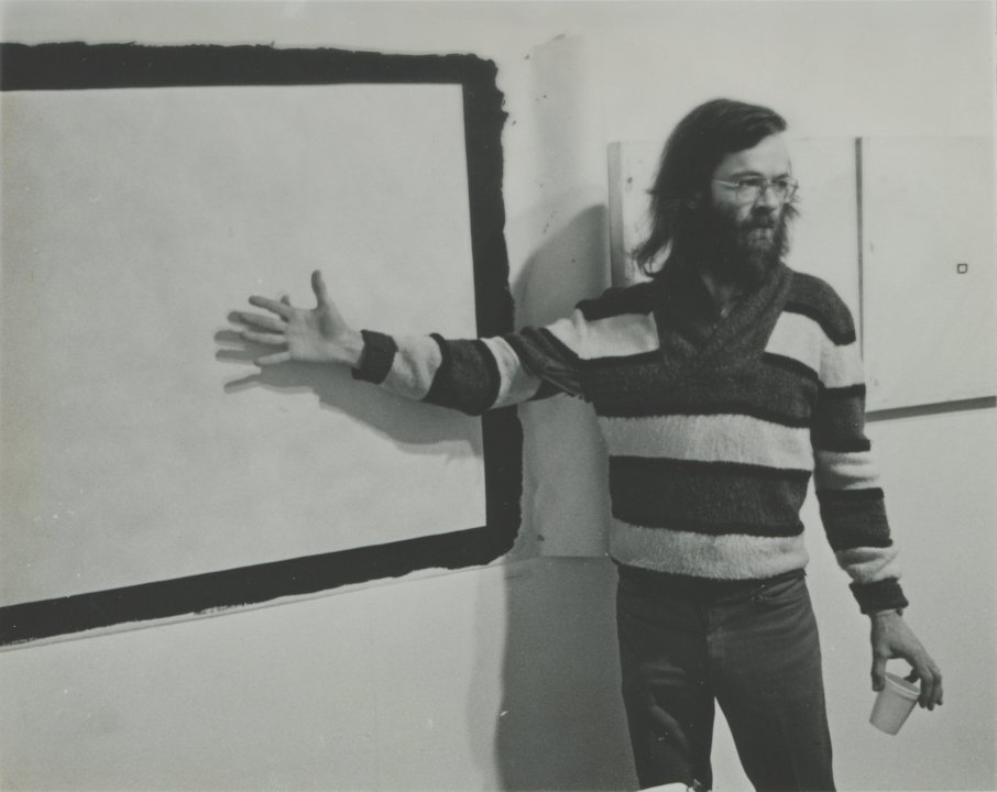 Tony Conrad in front of Yellow Movie 2/2/73, 1973, and two Yellow Movie—35mm Format canvases from 1973 in his retrospective exhibition at Hallwalls Contemporary Arts Center, Buffalo, New York, December 1977