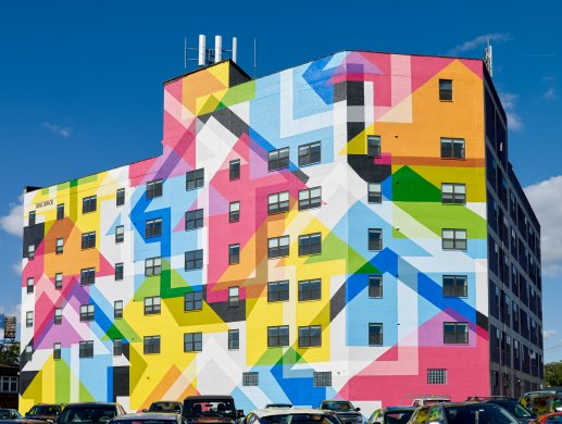 A large colorful mural with an arrow motif on the exterior wall of a large building