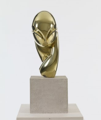 This abstracted portrait of woman's head and neck sits on a light grey stone cube. Its polished bronze surface is highly reflective. The head is an elongated egg shape, and its features are highly simplified and stylized. Two deeply cut arches, which meet at a sharp point at the bottom center of the head, define the woman's dramatic brow line and her eyelids. A teardrop form extending from the left side of the face suggests a hand resting against her cheek.