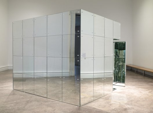 At center of this image is a cube covered with squares of mirrored tile. Four seamless rows of five tiles cover each face of the cube. An open doorway in the right corner leads into the interior. The interior, which is not visible in this installation image, is also entirely covered in mirrored tiles and features a mirrored table and chair.