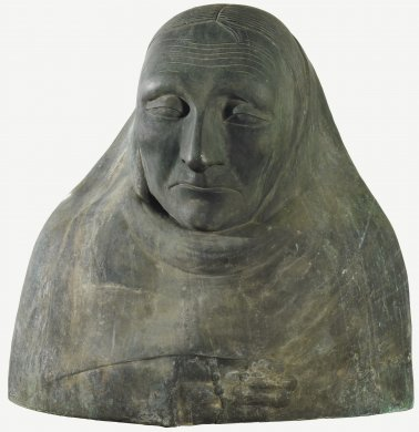 This mostly smooth surface of this bronze sculpture features the simplified facial features and shoulders of an old woman. She appears to be wrapped in a fabric garment so that only her face, the top of her head, and a portion of her right hand are visible. Beneath a lined forehead, her eyes are half open and her lips are set in a deep, weary frown.