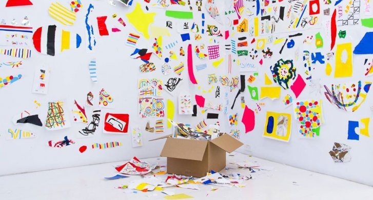Colorful drawings all over the walls in the corner of a room