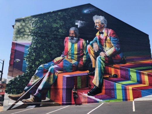 A large colorful mural on the exterior wall of a building featuring Mark Twain and John T. Lewis