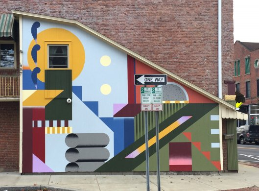 A colorful mural with geometric shapes in different colors on the side of a building