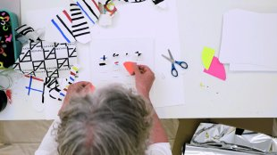 A bird's eye view of a man with gray hair placing a scrap of paper on a paper collage on the table in front of him