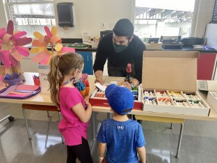A man helping two children pick out art supplies