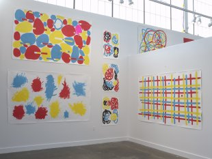 Installation view of colorful works on white walls in an industrial building