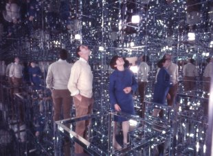 A man and a woman in a mirrored room looking up at their reflections in the ceiling