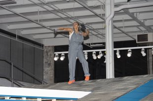 A woman in overalls dancing on a rooftop