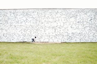 A Black woman drawing black lines on a large white exterior wall