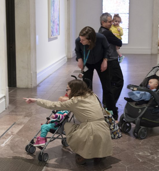 Parents with babies in strollers looking at art