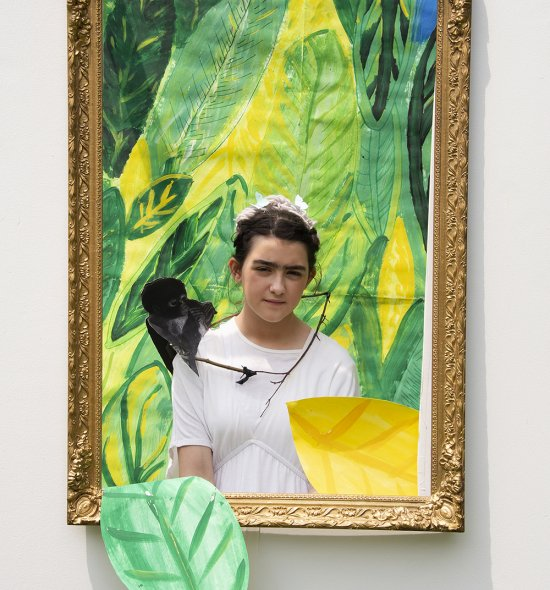 A girl with a stuffed monkey on her shoulder standing in front of a green painted backdrop