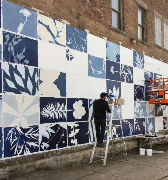 A mural on a large exterior brick wall featuring rectangles in different shades of blue with white plant shapes in the middle of each