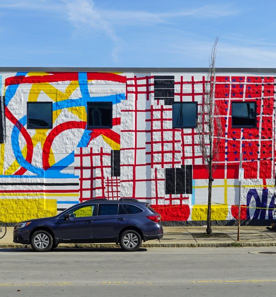 A mural featuring red, blue, and yellow lines, shapes, patterns, and blocks of color on a large exterior wall of a building