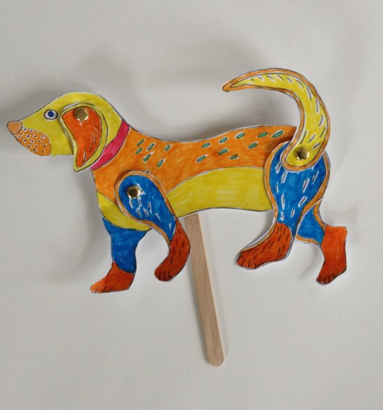 A colorful paper dog puppet on a popsicle stick