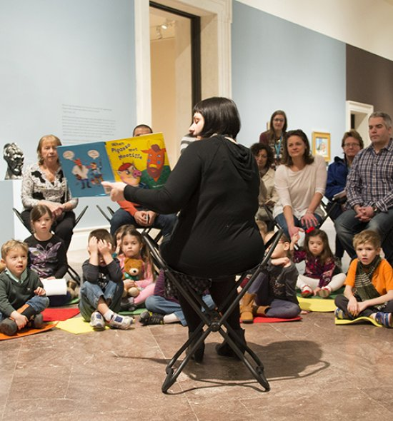 A curator reading a story to families in the galleries