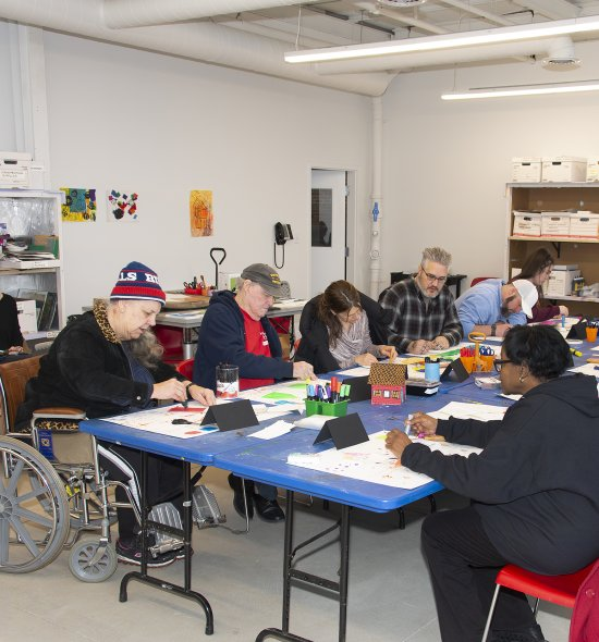 A group of adults, including one in a wheelchair, making art in a classroom