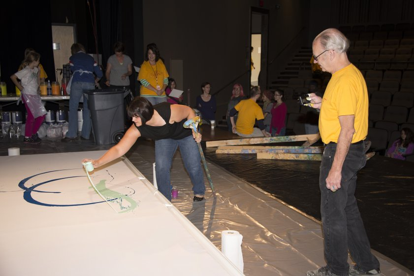 Participant Kari Achatz makes the first mark for Hamburg Arena Painting as Charles Clough watches