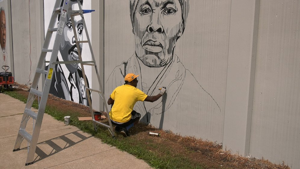 Artist Edreys Wajed at work on a portrait of Harriet Tubman for The Freedom Wall